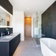 Master ensuite bathroom with floating vanity feature wall, stand alone porcelain bathtub, glass enclosed shower and walk-in closet