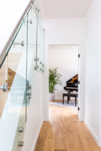 Picture of view from front entry door into main floor flex room with baby grand piano and large plant in a ceramic pot